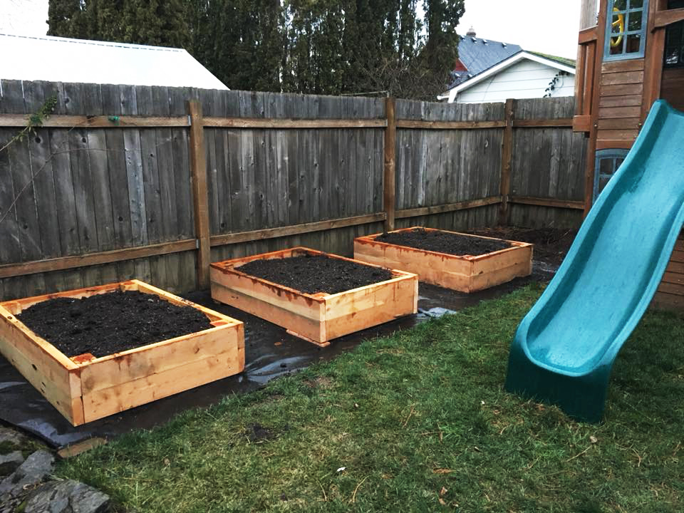 Three raised beds next to a childrens play house.
